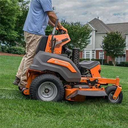 Husqvarna stand on mower sideview with driver