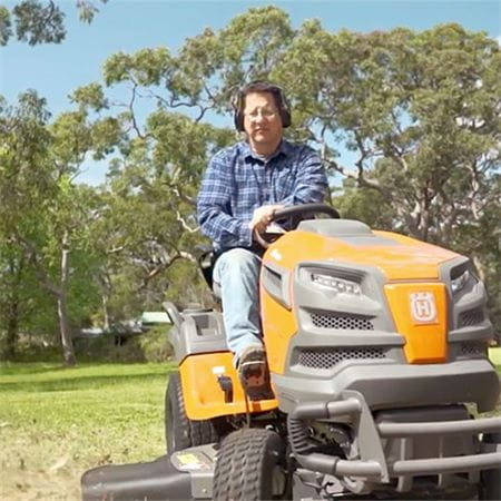A man riding a Husqvarna ride-on mower