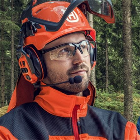 Man wearing Husqvarna PPE Helmet, hearing protection and gloves