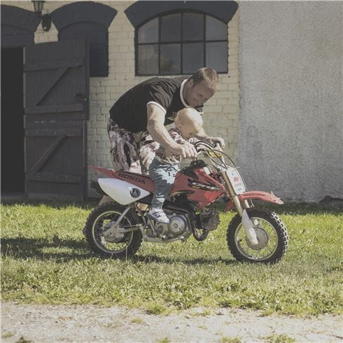 Jonsered man and child on mini motorcycle