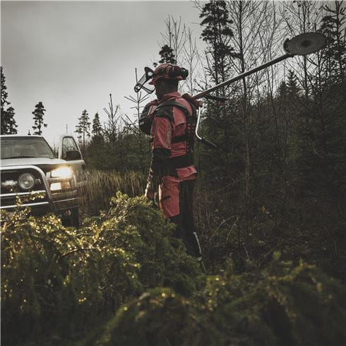 Jonsered man in forest with clearing saw and car