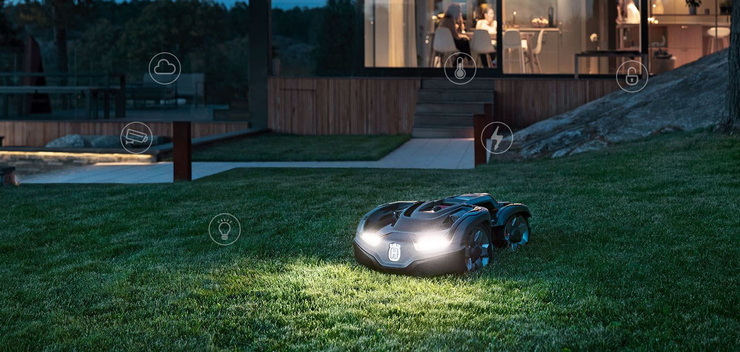 Husqvarna AWD Automower on lawn at night