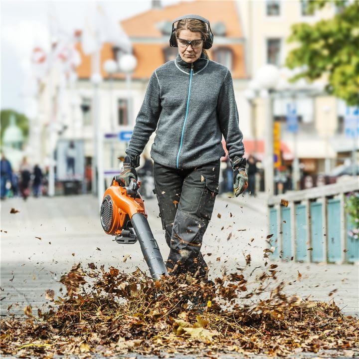 Woman with a hand-held leaf blower on a city street