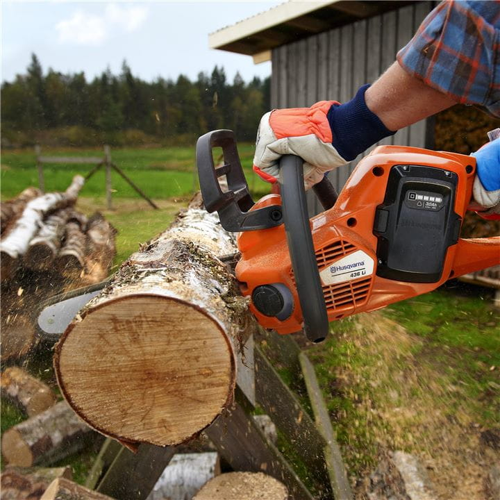 Battery chainsaw cutting firewood
