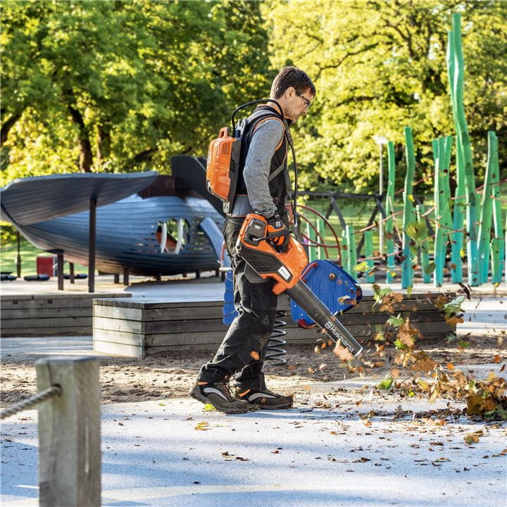 Man with a battery leaf blower on a play ground
