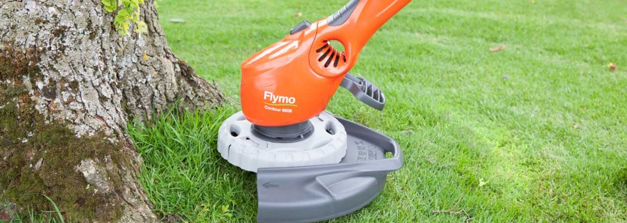 Flymo grass trimmer cutting close to tree