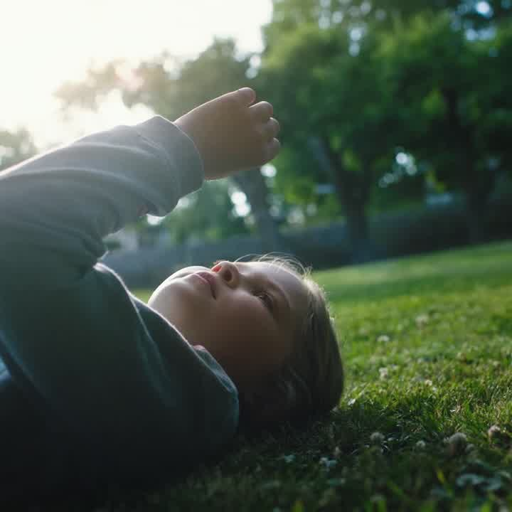 Child relaxing on lawn 6 sec 1x1 No text